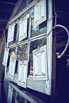 Rustic alternative to a traditional seating chart - beautifully designed table lists hung across an old window using twine and clothes pins.