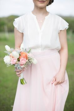 Instead of dresses for the bridesmaids, each bridesmaid wears a soft shirred blouse and long skirt. And look at those pretty pastel flowers.    Glamorous, Vintage, Rustic Texas Barn Wedding | Venue: Cherokee Rose