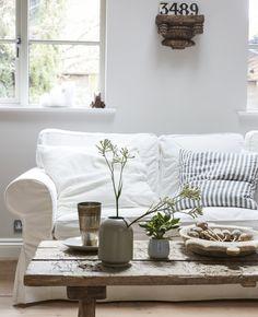 Ei stue i lyse farger med en hvit sofa og et rustikt salongbord i tre.