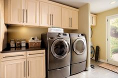 Sleek maple cabinets with bold metal accents impart a clean, uncluttered look to this modern laundry room.