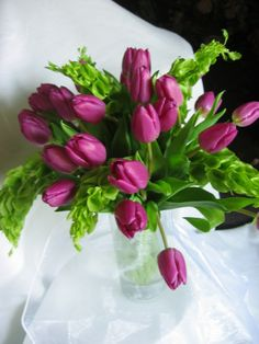 Pop of color in this bride's boquet.  Hot pink tulips with bells of Ireland. Lefrancois floral flowers wedding bouquet norwich ct. Use yellow tulips and add some blue