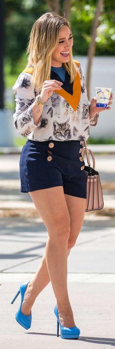 Who made  Hillary Duff's blue platform pumps, blue button shorts, pink handbag, and white cat print top?