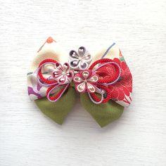 ✤ご覧頂きありがとうございます✤ ちりめん生地のりぼん(ポリエステル)に、正方形の小さな布を折りたたんで作るつまみ細工で作成した正絹の梅、3輪をUピンで添えました。リボンは縦約12cm、横約14cmでボリューム感があります。梅一輪の花の大きさは約3cmで...