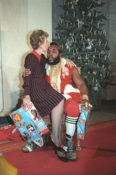 Former First Lady Nancy Reagan sitting on the lap of Mr. T dressed as Santa while kissing his forehead circa 1983.