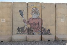 """A mural painted on blast walls outside the Navy-operated Role II emergency medical unit at Qayara Airfield West is pictured here on Wednesday, Aug. 30, 2017. The painting depicts Neptune, god of the sea, reaching out to combat troops, with the phrase """"Neptune healers"""" inscribed in Latin. (CHAD GARLAND/STARS AND STRIPES)"""