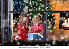 stock-photo-family-on-christmas-eve-at-fireplace-kids-opening-xmas-presents-children-under-christmas-tree-513519622.jpg 450×320 pixels