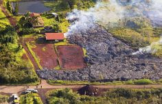This Monday, Nov. 10, 2014 photo released by The County of Hawaii via Ena Media Hawai'i/Blue Hawaiian Helicopters shows lava flow from the Kilauea Volcano near a residential structure in Pahoa, Hawaii. A stream of lava set a home on fire Monday in a rural Hawaii town that has been watching the slow-moving flow approach for months. (AP Photo/The County of Hawaii)