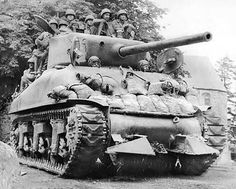 """3AD Sherman M4A1 (76mm) tank from the 32nd Armored Regiment equipped with a """"hedgerow cutter"""" & riders in Normandy, Aug. 1944.   WWII"""