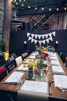 flowers. mismatched chairs. black fence. hanging lights. banner. wooden table.