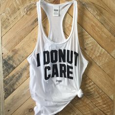 """VS PINK """"I Donut Care"""" Racerback Tank White tank with black print on front """"I DONUT CARE"""" & """"PINK"""") & back (image of PINK dog logo). Size S. Worn & washed ONCE. Tied in knot but can be worn untied, too. Selling because I don't wear it & need to clean out my closet. PINK Victoria's Secret Tops Tank Tops"""
