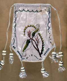 White silk purse trimmed with white silk cord and tassels, and silver sequins; one side embroidered in pink, brown, and green chenille in floral design; reverse has painted trophies of music, France, ca. 1799