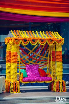 Real Indian Weddings - Divya and Dhiraj | WedMeGood | Orange and Yellow Genda Flower Swing for a Mehendi Function Picture Courtesy: DotDusk Studios #wedmegood #realwedding #genda #flowers