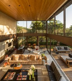 This living room with a double-height ceiling, opens up to the outside deck and swimming pool.