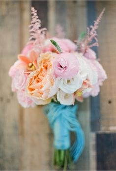 Consider Colored Yarn A punch of color in the form of blue yarn added a DIY touch to this delicate bouquet of peonies, ranunculus, veronica, astilbe and lisianthus designed by Poppy Love Weddings. Brides: 20 Ways to Wrap a Wedding Bouquet Beach Wedding Bouquets, Diy Wedding Flowers, Fall Wedding Dresses, Bouquet Pastel, Pastel Flowers, Flower Colors, Peach Bouquet, Bouquet Flowers, Peach Flowers