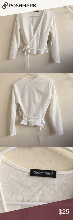 White Crepe Julliard Wrap Top White crepe textured fabric Julliard wrap top that ties around the waist. Deep V neck. Long sleeve. Size medium. American Apparel. New with tags.     🚫Trades 🚫Off posh transactions or 🅿️🅿️ 🚫negotiating in comments  🚷lowballs blocked ✅REASONABLE offers ✅Bundle for 30% off for 3 items or more. American Apparel Tops