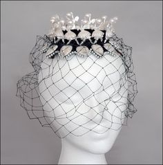 Bes-Ben 'Ballerina' hat   United States, ca. 1959   Black velvet crown with thirteen pearl edged points on which is a white leaf around the hat dance white ballerinas with arms raised holding a large pearl. Both leaves and ballerinas have a pearl finish. Black veil