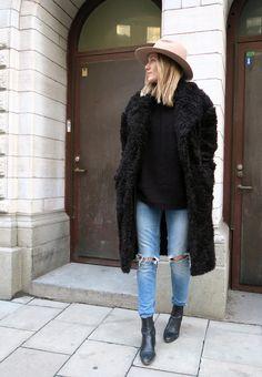 Black fake fur coat, black top, medium ripped jeans, beige hat, black leather boots