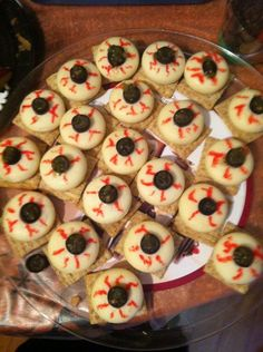 """Cheese Eye Balls: Baybell cheese, triscuit crackers, sliced black olives, green salsa (just a little in the middle of the olives"""" and a red food coloring pen. Cover with plastic wrap and cool until ready to serve & eat,"""