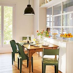 Office con pared acristalada, estantes de almacenaje y aparador con repisa en madera. Mesas de metal verde y mesa madera con patas torneadas.