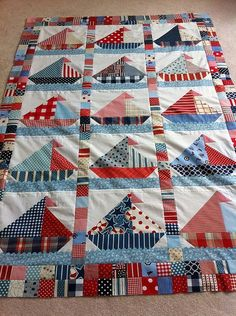 "scrappy sailboat Quilt using plaids, stripes, polkadots. in red white and blue. Quilt finishes 50"" x 80"". Sails made from various sized HST and waves made by rick rack."