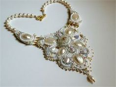 """This lovely embroidered necklace will highlight the sparkle in your eyes on your special day.  Freshwater pearls, mother-of-pearl cabochons, Czech and Japanese crystals, seed beads, gold plated toggle clasp.  Backed with soft, cream colored Ultrasuede. Measures 18"""" circumference; main pendant is 5"""" long and 3 1/2"""" wide."""