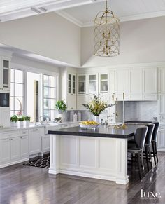 The classic and timeless kitchen includes painted cabinets by R&G Custom Crafting with polished-nickel pulls from Clyde Hardware Co. The perimeter Carrara marble countertops and Cambrian black granite island top are from Arizona Tile; the counter stools are by Swaim.