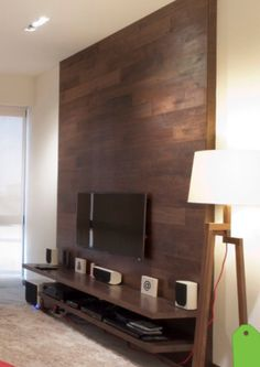 This TV wall is simple and effective. A shelf for equipment and a wooden wall to house TV and its wires.