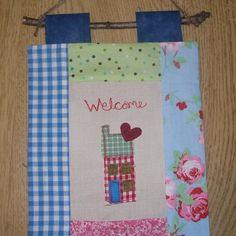 Welcome wall hanging £8 ♥  A patchwork wall hanging of a cute little house, made in raw edge machine embroidery, with a loving heart to welcome people to your home. Hangs from a twig with rustic twine loop.