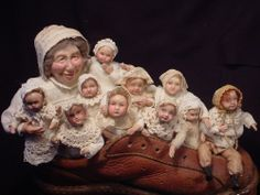 """Norma DeCamp Old Lady in Shoe with 10 little children. 10""""L leather shoe on wheels. Molded, hand-painted, & waxed little faces on armatured bodies dressed in antique cotton & lace. Adorable! (May 2014)"""