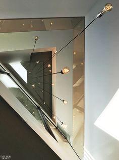 Custom pendant fixtures descend through a modern LA residence's triple height. #lighting #design #interiordesign #homes