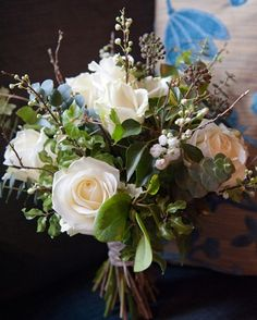 A natural hand tied bouquet of white roses, twigs, berried ivy by Orchard Designs www.hambletonweddingphotography.co.uk
