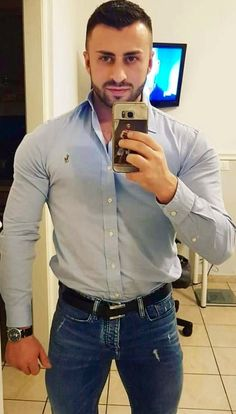 Taking a selfie in button down shirt and bulging jeans.