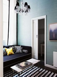 Serene living space punctuated with turquoise wallpaper, a crystal chandelier and a black and white chevron rug