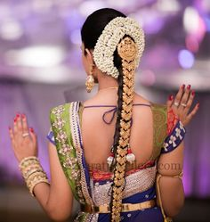 A South Indian Bride wearing antique finish work gold on her hair, combined with a Lakshmi pendant at the top! #Southindian #Bridal #hairstlye