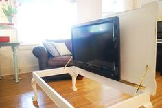 """A way to hide the tv in coffee table. I like this, but there aren't any directions; what to do with the cords and how they keep it from falling over, since it's obviously heavier on one side."" - Tip: A TV lift would have made this a whole lot easier and solved all of these issues!"