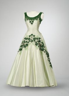 "This beautiful dress was designed by British couturier Norman Hartnell for Her Majesty Queen Elizabeth II. Her Majesty wore the gown on October 14, 1957 to a state banquet and reception at Rideau Hall in Ottawa, the official residence of the Governor General. Known as the ""Maple Leaf of Canada dress,"" it features a garland of green velvet maple leaves and white roses. The Canadian symbol of the maple leaf emphasizes Her Majesty's role as Queen of Canada."