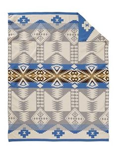 Curl up in this soft, warm throw blanket in a striking jacquard knit. Perfect for dozing off or draping across the sofa. Our intricate Silver Bark pattern features stylized stars, diamonds and arrows in a palette inspired by the white and grey bark of Aspen trees against a blue sky. - Pendleton Woolen Mills - National Cowboy Museum