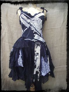 A handmade dress created from recycled fabrics.  The bodice has many layers of stitching, antique and vintage lace, black and white floral