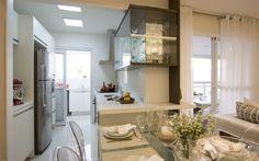 Interligada à sala pela mesa de jantar, que nasce após a bancada, esta cozinha projetada por Cilene Monteiro Lupi ainda tem passa prato ligado à varanda. Foto: Divulgação