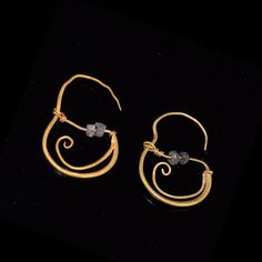 the slender style of these earrings are formed from rolled sheet gold which curves around, thickening towards the back where it splits to form a curved tail below. A thin wire, threaded with two glass
