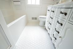 "2"" hexagon white ceramic tile, built-in cabinetry, Capital lighting soho sconces, crown moulding, custom mirror, Jacuzzi Linea soaking tub, Kohler Cimarron toilet, Kohler Tides self rimming sink, Moen Dartmoor 4"" center faucet, Moen Dartmoor towel bar, Moen Wynford tub valve, onyx countertop, SW 9066 agapanthus"