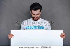 Please help to community! Confident young man in volunteer t-shirt holding white board and looking at it with smile while standing against grey background - stock photo
