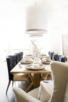 Upholstered chairs, rustic timber table, wicker plates and low hanging pendants....