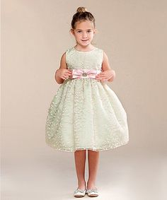 This charming dress delights budding princesses with its twirl-ready skirt and sweet bow accent.