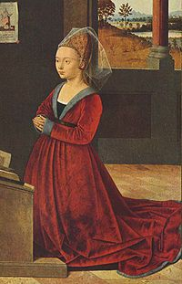 Fur-trimmed Burgundian gown of mid-15th century has a V-neck that displays the black kirtle and a band of the chemise. Hair is pulled back in an embroidered hennin and covered by a short veil.