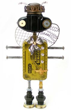 """Buzzinga"" Height: 17"" Principal Components: Candied ginger tin, Kodak 127 camera, oil lamp burner, molly bolts, whisks, clock gears..."