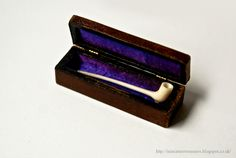 Miniature Treasures: pipe carved of ivory, silk lined box.