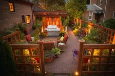 This comely garden setting in this small home's backyard shows how careful planning can produce an outstanding design. K&D Landscape Management used unusual wood fencing material for the pergola and to line the perimeter of the yard and added colorful small and large scale plants for balance and interest. A well-conceived lighting plan, as seen here, produces a dramatic effect.