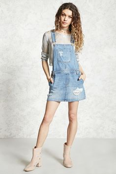 A denim overall dress featuring adjustable straps, a bib patch pocket, triple button side closures, four-pocket construction, and distressed details throughout.