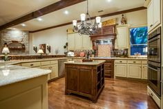 Great, open kitchen // Beamed ceiling, yellow cabinetry, brown island, stainless appliances